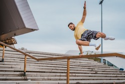 Man doing sports and training outdoors in city. Man jumping over the fence and working out hard. Parkour elements in workout.