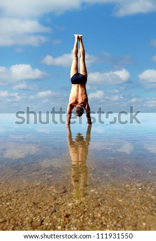 Man doing vertical handstand into the sea water