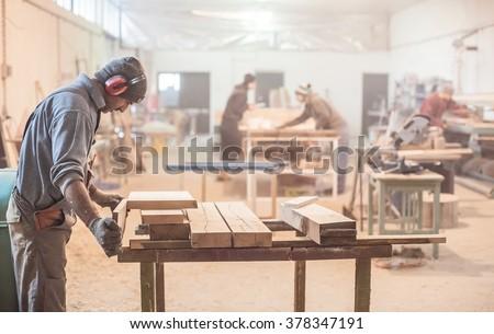 Man doing woodwork in carpentry. Carpenter work on wood plank in workshop
