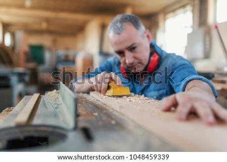 Man doing woodwork in carpentry. Carpenter work on wood plank in workshop. Smiling woodworker. Attractive man doing woodwork in carpentry. Profession, carpentry, woodwork and people concept