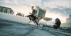 Man doing workout using resistance parachute on rooftop. Side view of a fitness man running with a resistance parachute on terrace of a building.