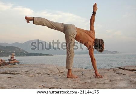 Man doing yoga outdoors. Ardha-Chandrasana. Side view.