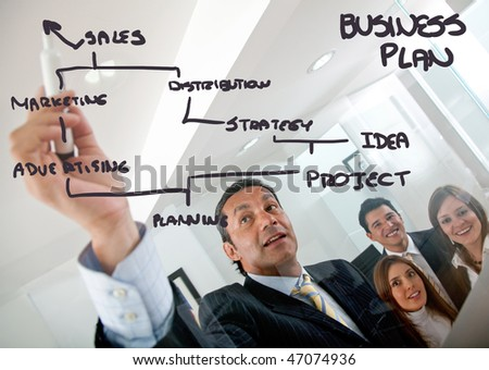 man drawing a business plan and showing it to a group - stock photo