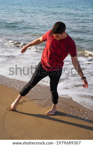 Man drawing a circle with his foot on the seashore. He is barefoot and his trousers are rolled up. It is a sunny day and the sea is blue. He is balancing on one leg. Les Marines, Denia. Photo stock ©