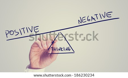Man drawing a seesaw showing an imbalance between Positive - Negative - Thinking with the word positive being weighted more than the word negative on opposites ends with Thinking as the fulcrum.