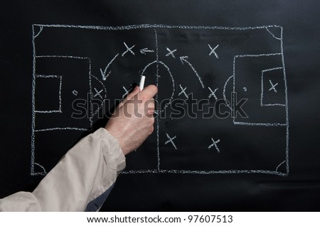 Man drawing a soccer game tactics and strategy with white chalk on a blackboard. - stock photo