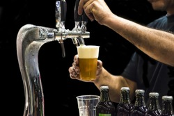 Man drawing beer from tap in an plastic cup. Isolated in a black background