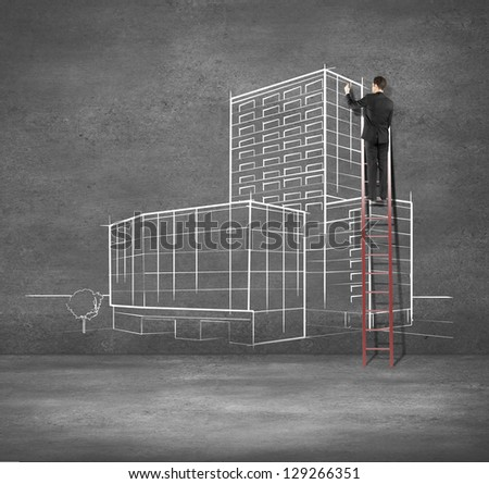 man drawing building on concrete wall