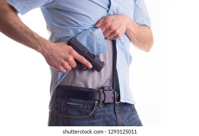 Stock photo of a man drawing concealed carry pistol from a waist band holster.