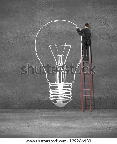 man drawing lamp on concrete wall