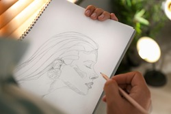 Man drawing portrait with pencil in notepad indoors, closeup