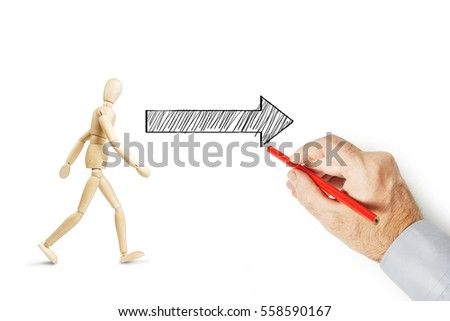Man draws an arrow and shows the way where to go. Conceptual image with pencil drawing #558590167
