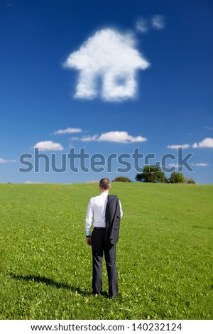 Man dreaming of a new home standing with his back to the camera and his suit jacket slung over his shoulder facing out over a green field with a cloud in the shape of a house in the blue sky