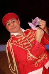 Man dressed as circus clown holding euros