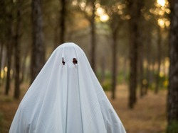 man dressed as ghost in a forest celebrating halloween