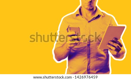 Man dressed casually in collared shirt using a tablet and phone -  Casual business concept image with copy space for text. #1426976459