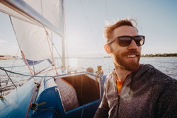 Man dressed in casual wear and sunglasses on a yacht. Happy adult bearded yachtsman close-up portrait. Handsome sailor on a boat smiling during regata on a sea or river.