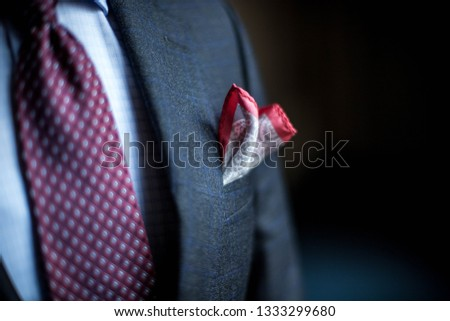 Man dressed in Dark blue suit coat with burgundy polka dot ties and white shirt, red and white pocket square. #1333299680