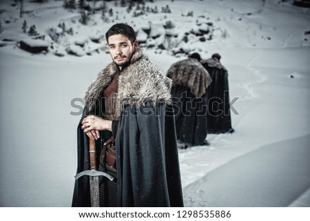 Man dressed in medieval armor and raincoats with swords in winter at the mountains under snow blizzard  #1298535886