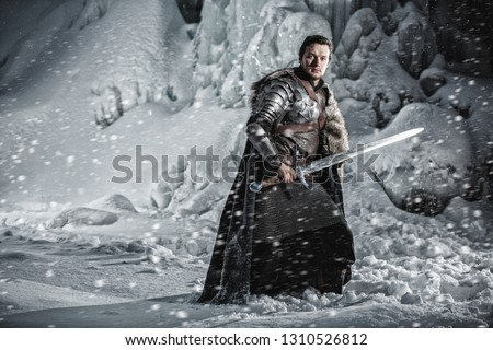 Man dressed in medieval armor and raincoats with swords in winter in the mountains under heavy snow blizzard. Fantasy warrior knights in winter snowy landscape