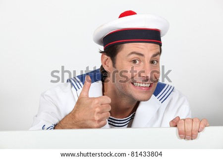 Man dressed in sailor costume with message board