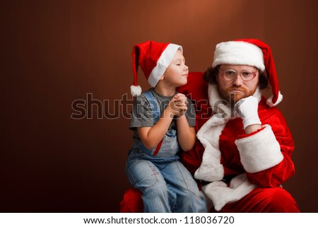 Man,dressed in Santa costume looks tired and unhappy Boy is  sitting on Santas knee and asking about his  present.  Brown background,copyspace