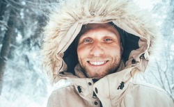 Man dressed in Warm Hooded Casual Parka Jacket Outerwear walking in snowy forest cheerful smiling face portrait. Outdoor time and winter outfit concept image.