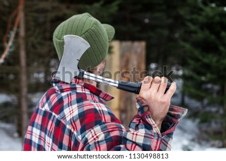 Man dressed in winter clothes holds an axe in front of a wooden board as part of an axe throwing competition