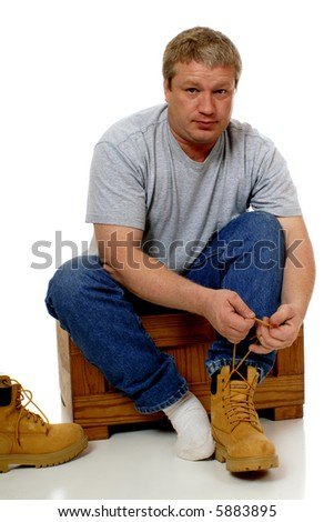 Man dressing for construction job, putting on his workboots.