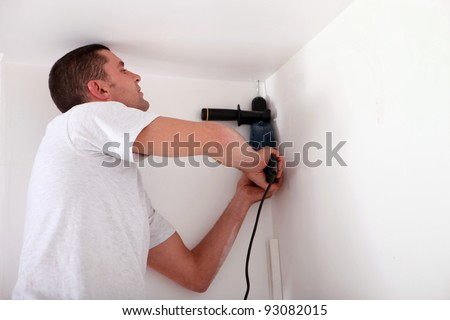 Man drilling a ceiling