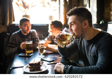 Man drink beer in front of to discussing drinking friends in pub.