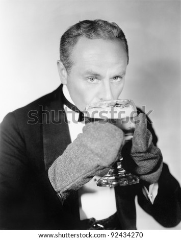 Man drinking a big glass of cold beer with mittens