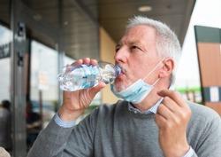 Man drinking a bottle of water during coronavirus pandemic