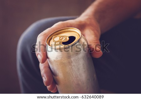 Man drinking a cold beer after work in the evening. Hand holding a aluminum can. #632640089