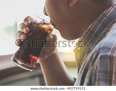 Man drinking a glass of soda with ice