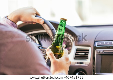 man drinking alcohol while driving the car #409451983
