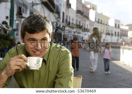 man drinking cappuccino with family in the background