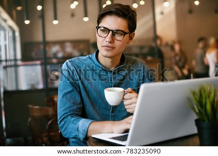 Man Drinking Coffee And Working On Notebook In Cafe. Portrait Of Young Male In Stylish Glasses And Casual Clothes Drinking Coffee And Using Laptop In Cozy Coffee Shop. High Resolution. #783235090