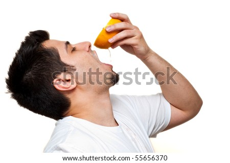 man drinking out of grapefruit