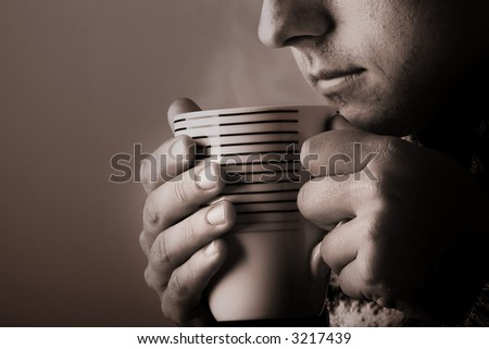 Man drinking warm beverage. Low key image. Sepia toned. Steam from cup