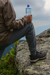 Man drinking water after hiking in mountain. Man holding a bottle on the beautiful mountains background. Close up of a man drinking water from a bottle outside. Adventure man with water near the wood.