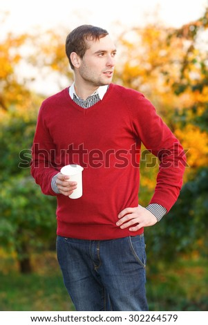 Man drinks coffee from a paper cup in the autumn park. Happiness people, drink and fast food concept - man in hat with takeaway tea or coffee cup. Calm. Drink coffee break. Street food.