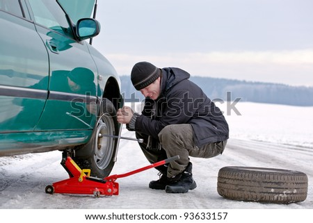man driver having trouble at road changing wheel, repairing car, unscrewing bolts