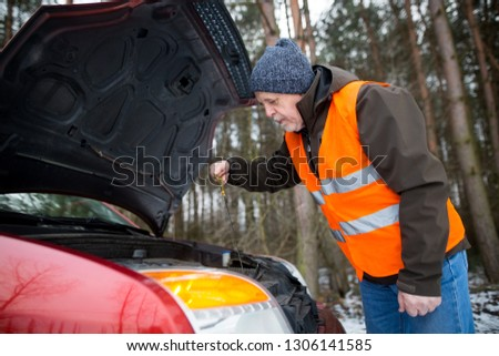 man driver wearing a high visibility vest  bending over the engine of his broken down car during winter time #1306141585