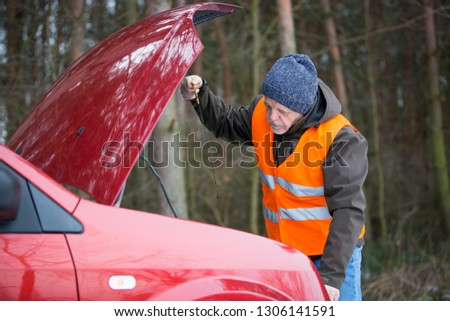 man driver wearing a high visibility vest  bending over the engine of his broken down car during winter time #1306141591