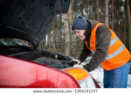 man driver wearing a high visibility vest  bending over the engine of his broken down car during winter time #1306141597