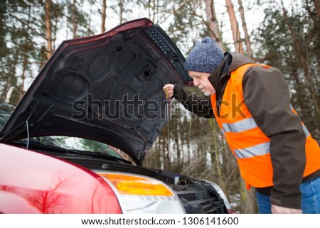 man driver wearing a high visibility vest  bending over the engine of his broken down car during winter time #1306141600