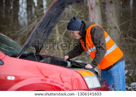 man driver wearing a high visibility vest  bending over the engine of his broken down car during winter time #1306141603