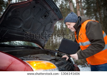 man driver wearing a high visibility vest  bending over the engine of his broken down car during winter time #1306141606