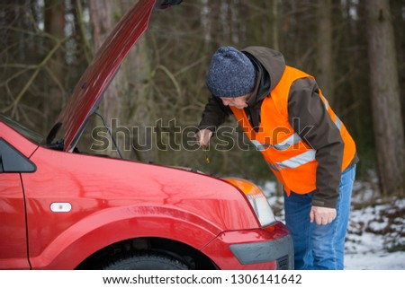 man driver wearing a high visibility vest  bending over the engine of his broken down car during winter time #1306141642